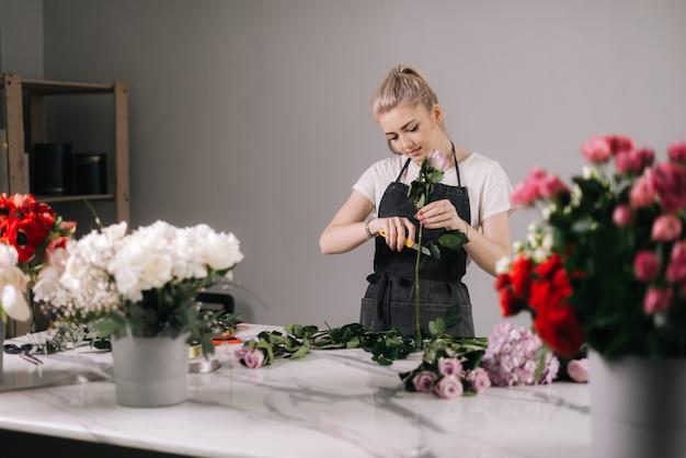 테이블에 꽃다발에 신선한 장미를 절단 앞치마를 입고 예쁜 젊은 여자 꽃집