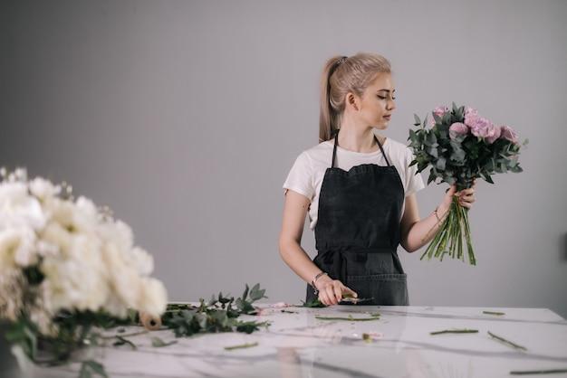 테이블에 꽃다발을 들고 앞치마를 입은 예쁜 젊은 여성 꽃집