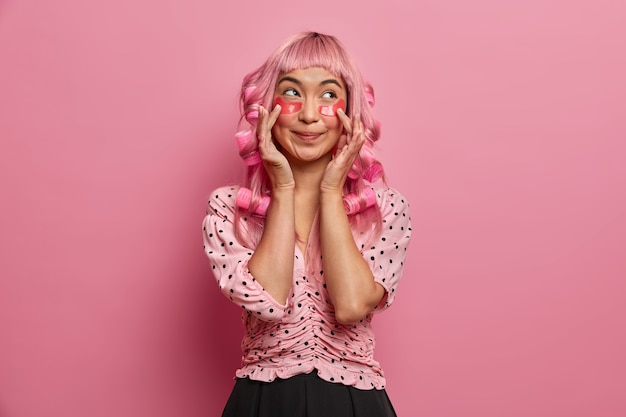Pretty young woman gets pink hair curled, applies curlers, beauty patches under eyes, being well dressed