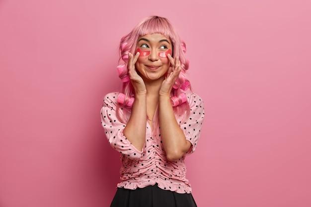 예쁜 젊은 여자가 분홍색 머리카락을 웅크 리고, curlers를 적용하고, 눈 아래에 미용 패치를 적용하고, 옷을 잘 입습니다.