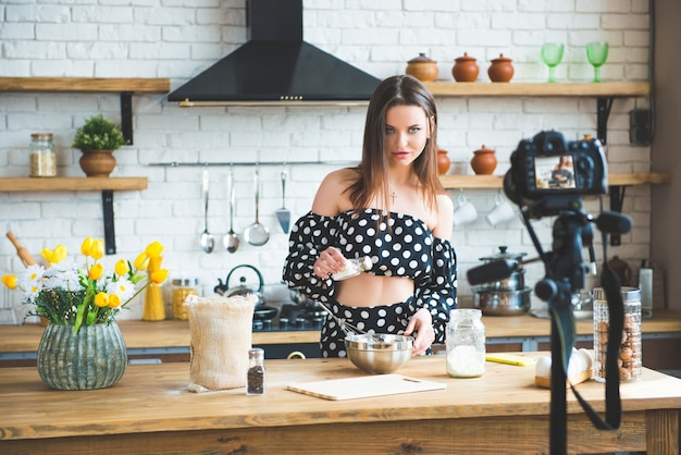 Pretty young woman girl food blogger in polka dot dress working on a new video and explaining how to cook a dish.