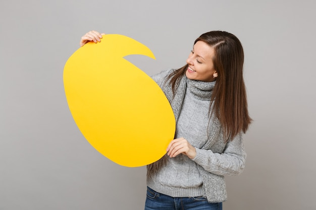 Pretty young woman in gray sweater, scarf looking on yellow empty blank say cloud, speech bubble isolated on grey background. healthy fashion lifestyle, people sincere emotions, cold season concept.