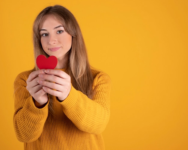 Pretty young woman happy with a red heart in her hands, yellow space