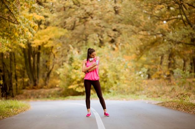 Довольно молодая женщина отдыхает во время тренировки в осеннем лесу