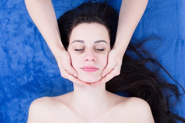 Довольно молодая женщина имеет массаж лица, косметолог в спа-центре