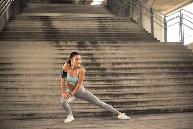 Милая молодая женщина имея тренировку в городской среде