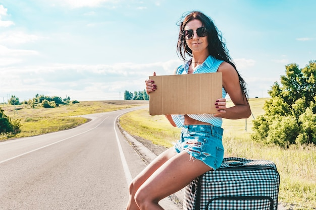 道に沿ってヒッチハイクし、スーツケースと空の段ボール皿を持って田舎道で待っているかなり若い女性。サングラスヒッチハイカーの美しい少女。空のボード