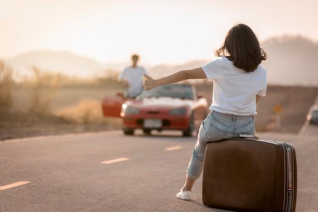 Довольно молодая женщина, путешествующая автостопом по дороге