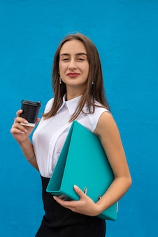 예쁜 젊은 여성이 컵 폴더를 잡고 흰색 셔츠와 검은색 치마를 격리하고 있습니다.