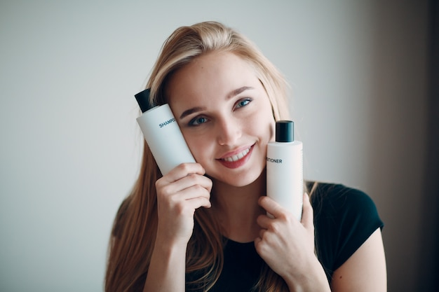 Pretty young woman hold two bottle with empty space. shampoo and conditioner.