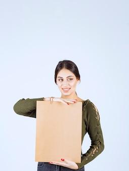 흰색 바탕에 종이 가방을 들고 꽤 젊은 여자.