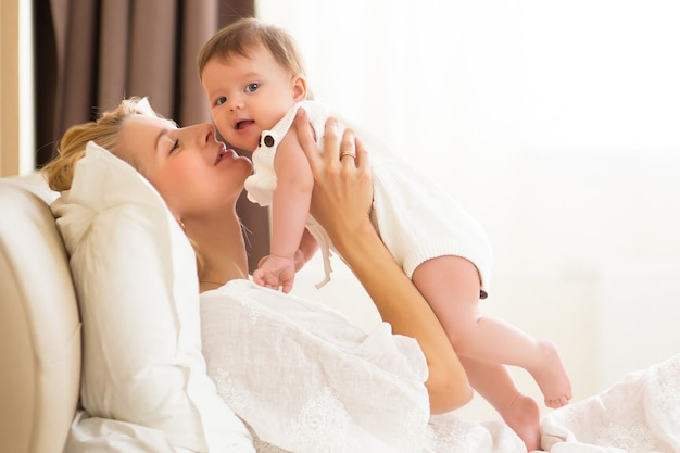 Pretty young woman holding baby girl in her arms at domestic room at the morning. happy mother hugging and kissing her little newborn daugther at home on white bed