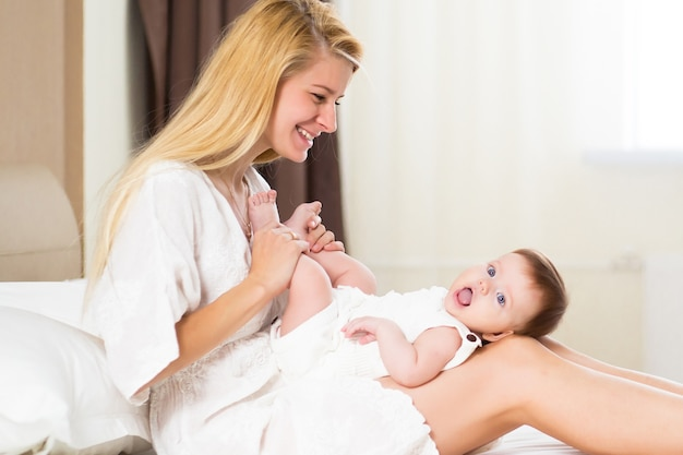 Pretty young woman holding baby girl in her arms at domestic room at the morning