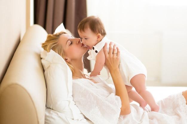 朝、国内の部屋で女の赤ちゃんを腕に抱くかなり若い女性。幸せな母親は白いベッドの上で自宅で彼女の小さな新生児の娘を抱きしめてキスします