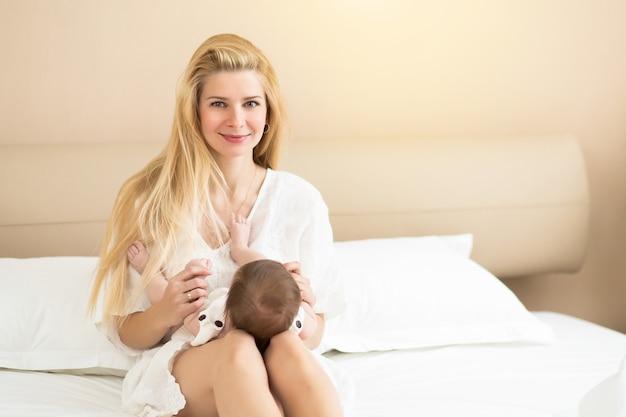 朝の国内の部屋で彼女の腕の中で女の赤ちゃんを保持しているかなり若い女性