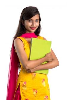 Милая молодая женщина держа книгу и представляя на белизне
