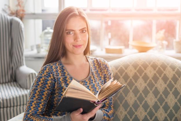 Милая молодая женщина держа книгу в руке смотря камеру