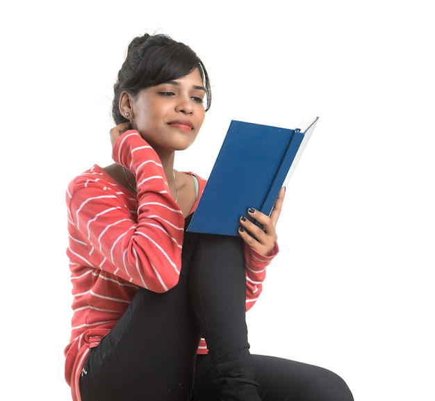 Pretty young woman holding book and posing on white