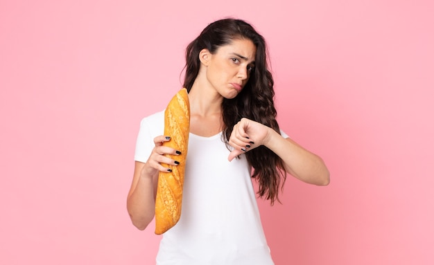 Pretty young woman holding a bread baguette