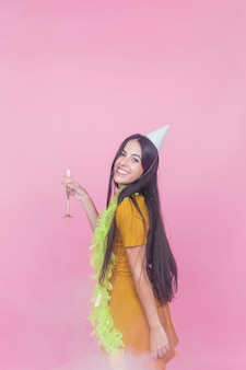 Pretty young woman holding champagne flute posing against pink background