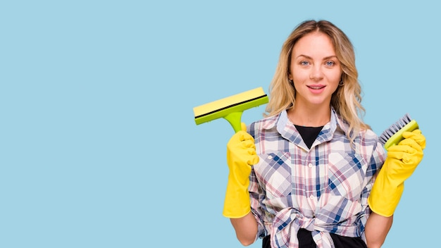 Pretty young woman holding cleaning supplies against blue background