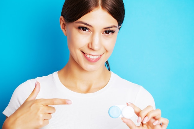 Pretty young woman holding a container with contact lenses for eyesight