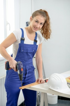 Pretty young woman holding  cordless drill