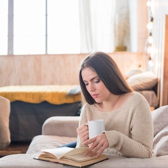 Pretty young woman holding cup of coffee reading book