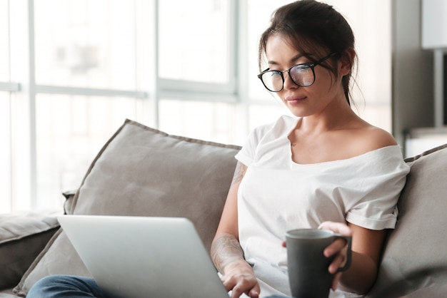 Pretty young woman holding cup of coffee using laptop computer.