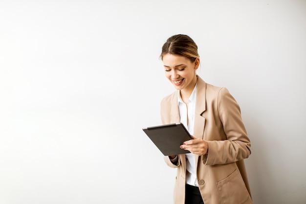 Довольно молодая женщина, держащая цифровой планшет у белой стены в современном офисе