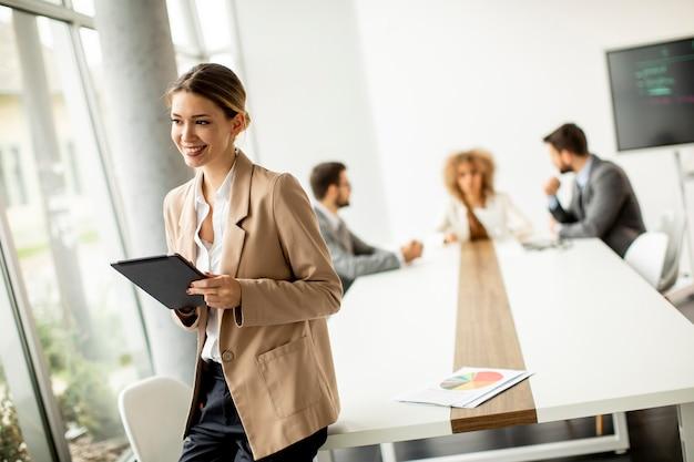 Довольно молодая женщина, держащая цифровой планшет в современном офисе перед своей командой
