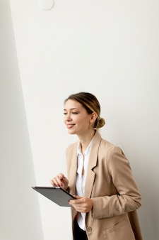 Довольно молодая женщина, держащая цифровой планшет в современном офисе