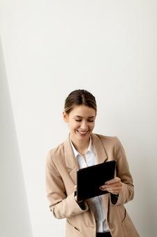 Довольно молодая женщина, держащая цифровой планшет в современном офисе Premium Фотографии
