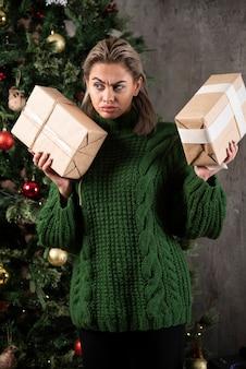 Довольно молодая женщина, держащая подарочную коробку возле елки