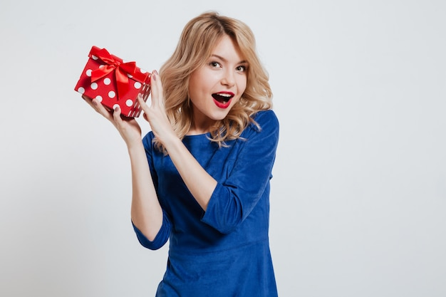 Pretty young woman holding gift box over white wall