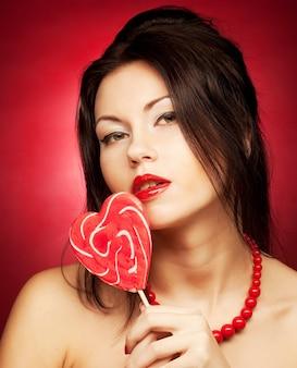 롤리 팝을 들고 예쁜 젊은 여자. 빨간색 배경 위에.