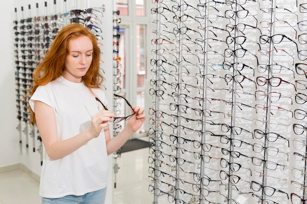 Pretty young woman holding and looking at spectacle in optics shop