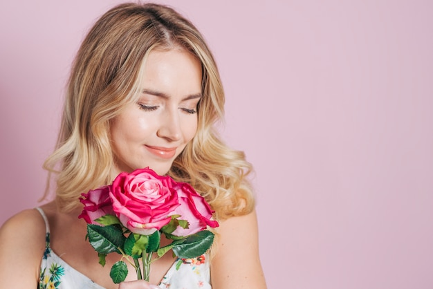 Pretty young woman holding pink roses in hand against pink background