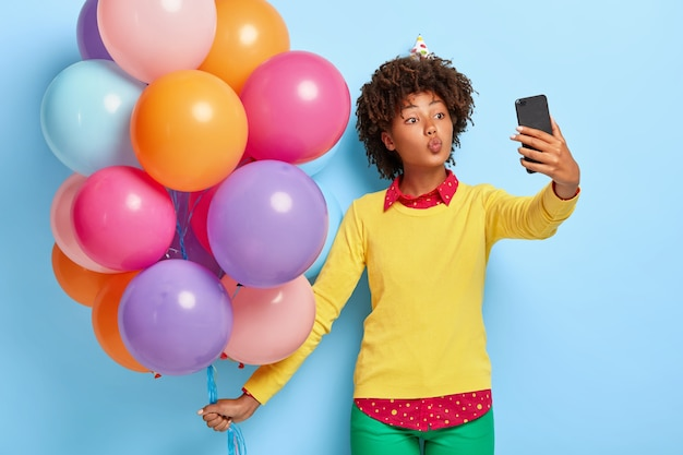 Pretty young woman holds multicolored balloons while posing in a yellow sweater