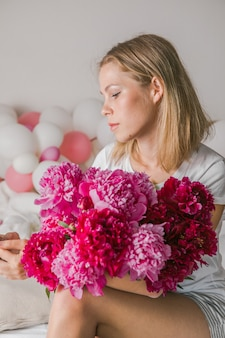 Pretty young woman  at home  in bedroom in bed holding flowers take a selfie by mobile phone