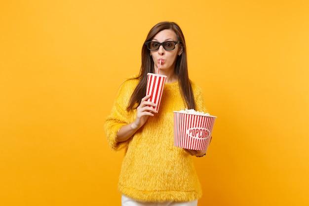 3d 아이맥스 안경을 쓴 예쁜 젊은 여성이 팝콘 양동이를 들고 노란색 배경에 격리된 플라스틱 컵에서 콜라나 소다를 마시는 영화를 보고 있습니다. 영화, 라이프 스타일에서 사람들은 진실한 감정.