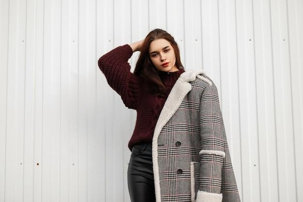 모피와 유행 체크 무늬 긴 재킷에 예쁜 젊은 여자