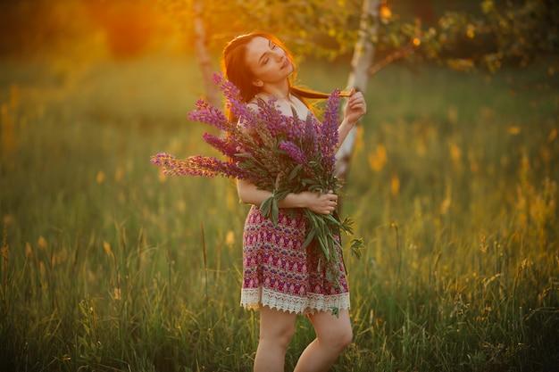Милая молодая женщина в поле на заходе солнца. держа цветы