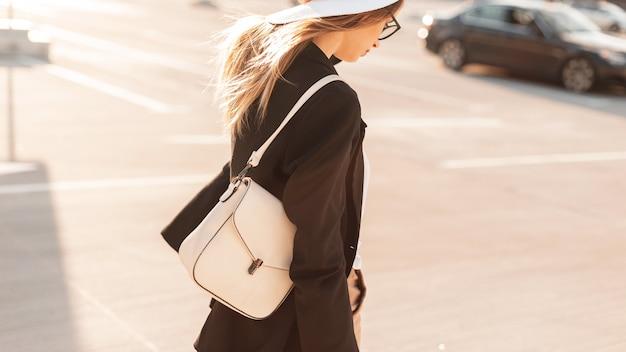 해질녘 거리를 걷고 있는 흰색 유행 가방을 든 모자와 안경을 쓴 예쁜 젊은 여성. 가죽 가방의 패션 여름 컬렉션