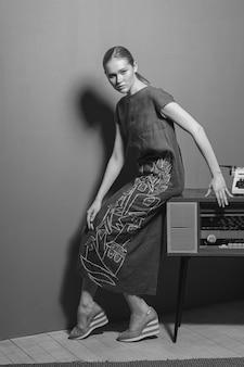 長いドレスのポーズでかなり若い女性。白黒の縦長の画像。