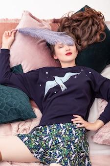 ベッドに横になって楽しんでいるスタイリッシュなホームウェアのかなり若い女性。トップダウンビュー。