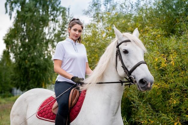 トレーニング中に白い純血種の競走馬の背中に座っている間あなたを見ているアクティブウエアでかなり若い女性