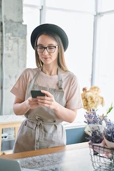 スタジオでクライアントの注文を処理しながらスマートフォンでエプロンと帽子のメッセージングでかなり若い女性
