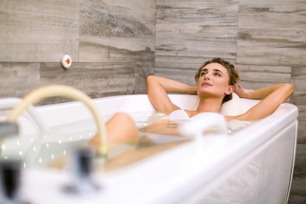 ビューティースパサロンでハイドロマッサージ中にお風呂でかなり若い女性、リラックスして見上げる。水中ハイドロセラピーマッサージ手順