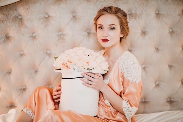 花が付いているベッドでかなり若い女性